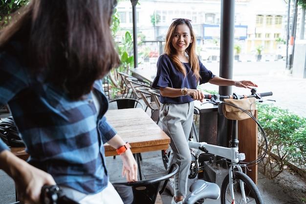 Встреча двух молодых женщин-велосипедистов в кафе