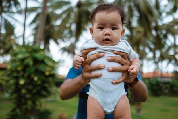 父は彼の赤ちゃんを屋外で運ぶ