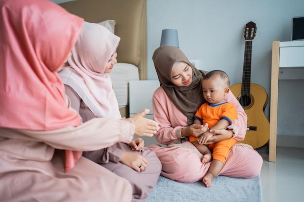 彼女の友達とアジアのイスラム教徒の母親は床に座っているとき彼女の息子と一緒に遊んで楽しんでいます