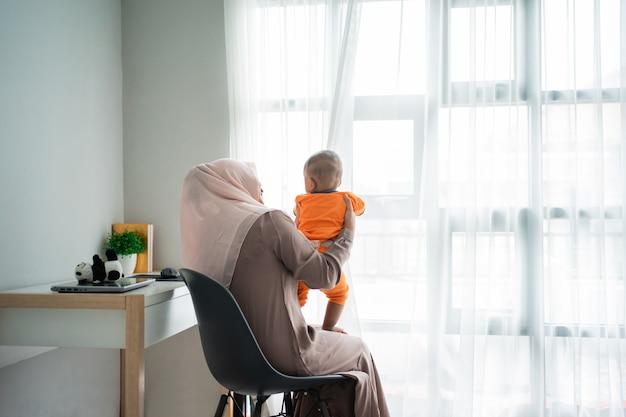 一緒に遊ぶときに膝の上に彼女の小さな男の子を保持しているアジアのイスラム教の母