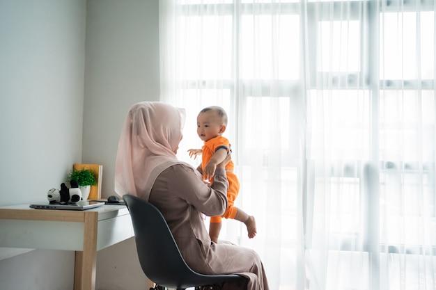 椅子に座りながら遊んでいるときに膝の上に息子を抱く母親