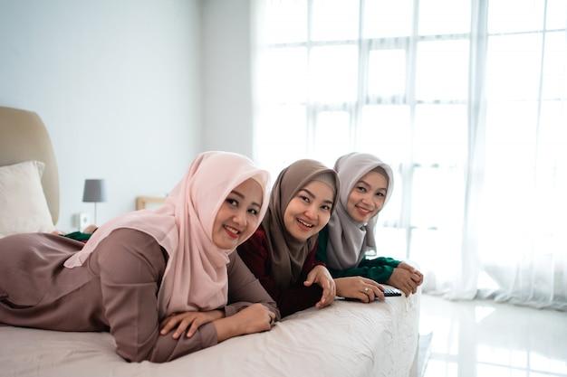 ベッドに横になっている友達とアジアのヒジャーブ女性がテレビを見てお楽しみください。