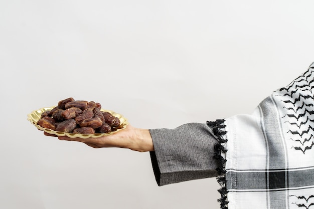 Рука крупным планом держит даты фрукты