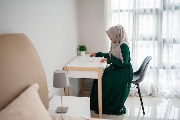 椅子に座ってアルコーランの聖典を読んでいるヒジャーブの女性