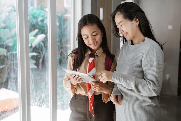Мать дочь с помощью планшета вместе дома