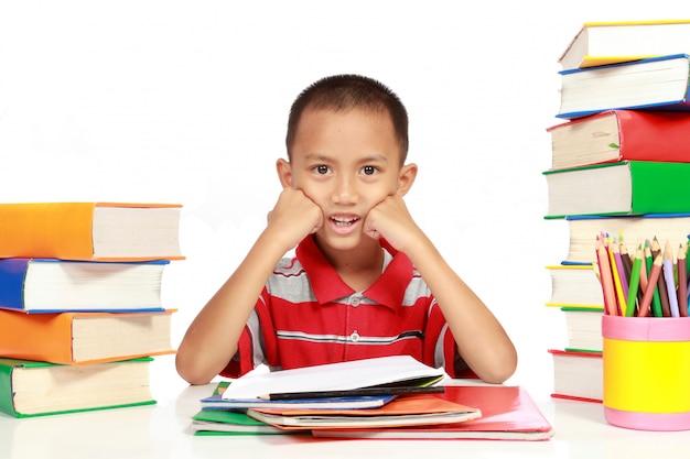 宿題を持った少年と彼の周りにたくさんの本