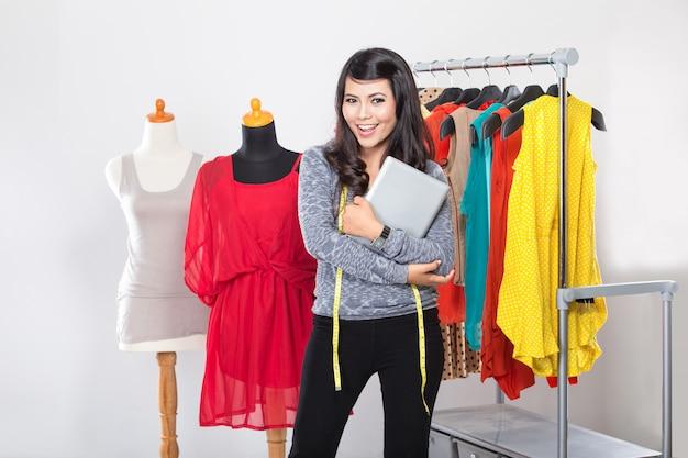 Молодая азиатская дизайнерская женщина держит планшет, улыбаясь, смотрит на го