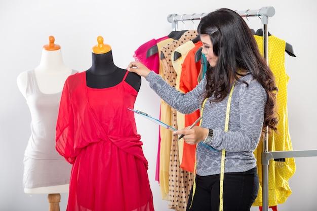 Молодой азиатский дизайнер держит ткань, глазируя ее в манекен