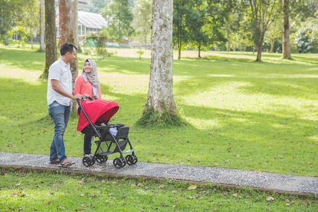 Мать и отец, толкая коляску в парке