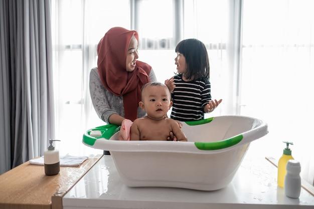 姉は母親が赤ん坊の兄弟を洗うのを助けます