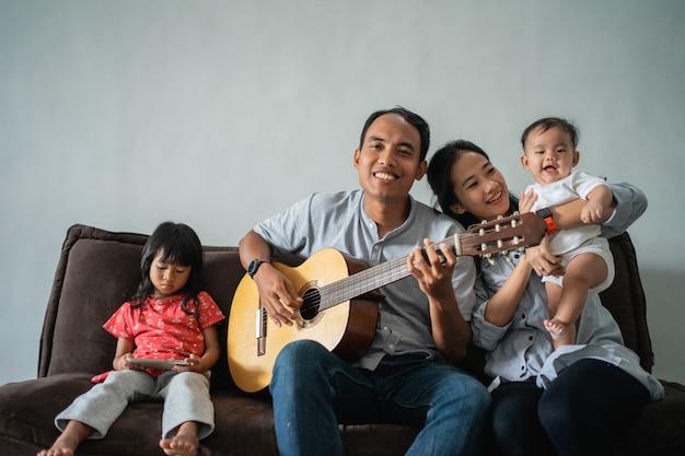 父は家族と一緒にソファーでギターを弾く