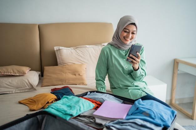 Азиатская мусульманская женщина, используя ее мобильный телефон с полным чемоданом