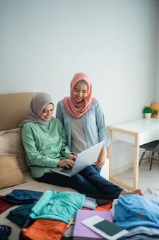服でいっぱいのベッドでラップトップを使用してアジアのイスラム教徒の女性