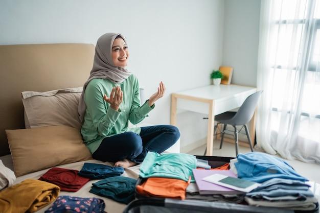 服でいっぱいのベッドで祈るイスラム教徒の女性