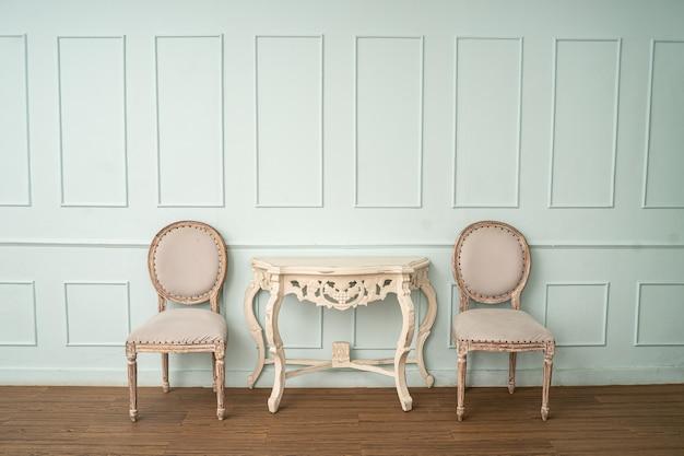 Винтажный стол и стул на светло-зеленой стене