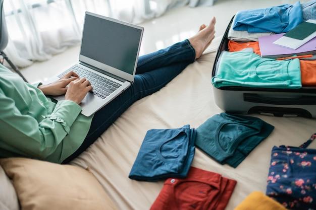 完全なスーツケースとラップトップを使用してヒジャーブ女性