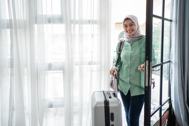 イスラム教徒の女性旅行者が彼女のバッグとスーツケースでドアの入り口を開く