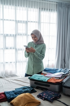 完全なスーツケースで彼女の携帯電話を見てアジアのイスラム教徒の女性