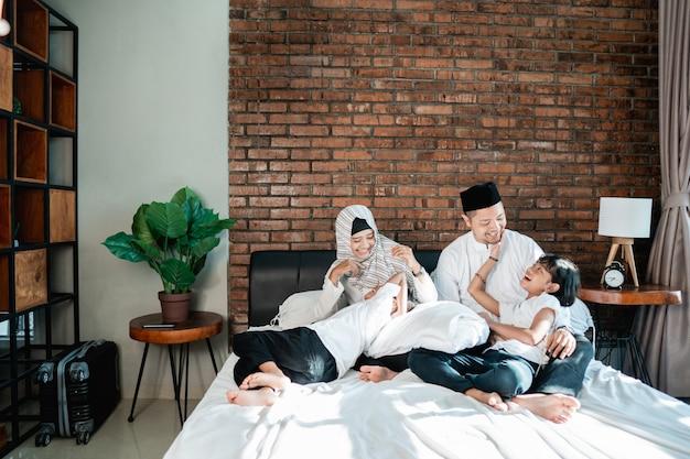 子供を持つアジアの家族はベッドでリラックスして冗談を言っています