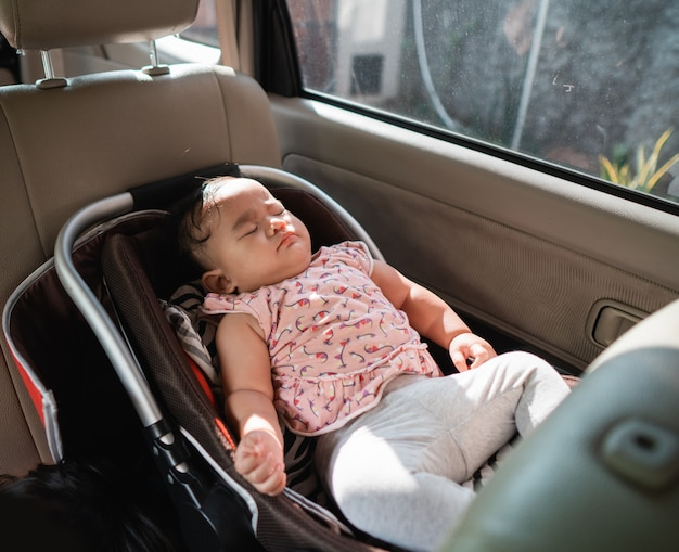 車の椅子に座って眠っている赤ちゃん