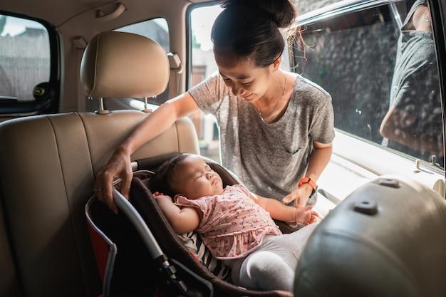 アジア人の母親がベビーチェアを固定