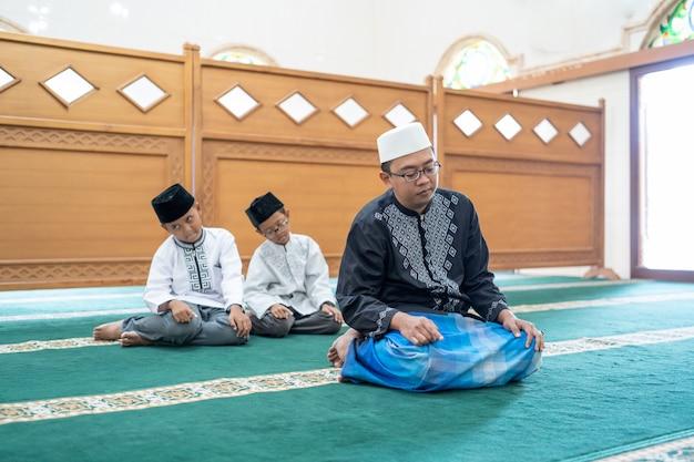 Отец и сын вместе молятся в мечети