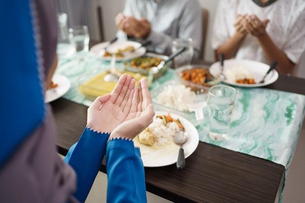 Мусульманская семья вместе молится перед едой