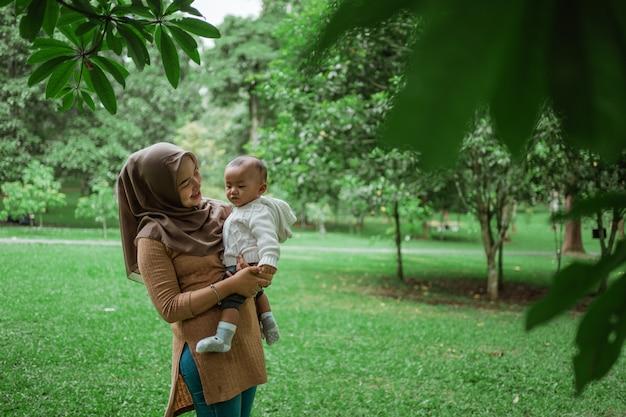 小さな赤ちゃんを抱いてヒジャーブ女性