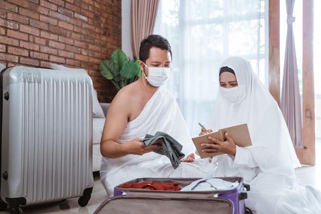 イスラム教徒の巡礼者の妻と夫がアイテムを準備します。