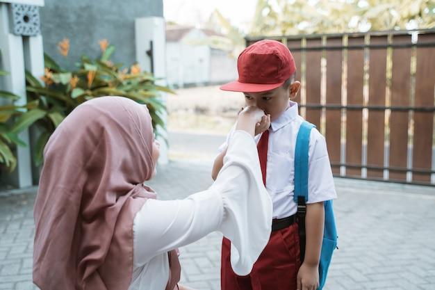 子供は学校の前に彼の母親の手を振ってキスします