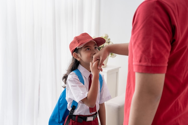 アジアの子供が学校に行く前に彼女の父親の手にキス