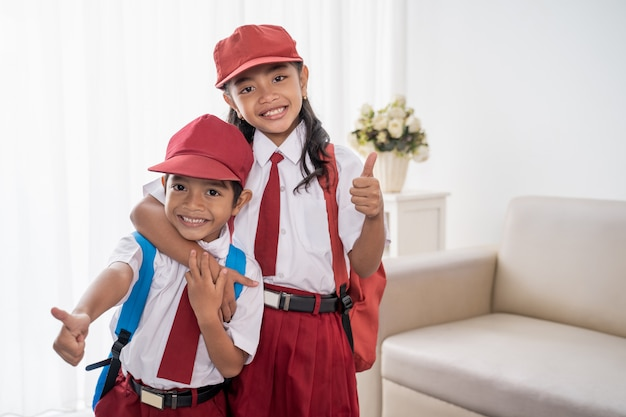 Ученик начальной школы в школьной форме показывает палец вверх