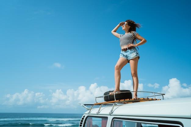 美しい女性は、屋根の上に立って遠征自然を楽しむ