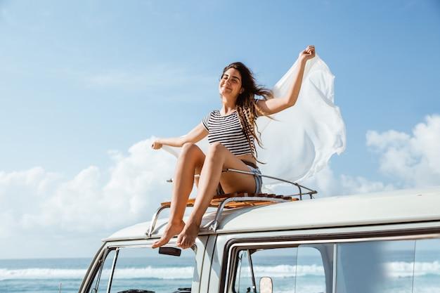 美しい女性は、屋根の上に座って遠征自然を楽しむ