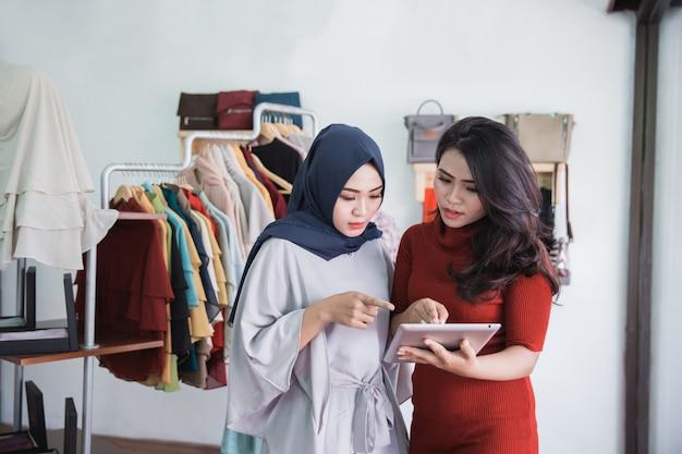 Две женщины с помощью планшета в магазине модной одежды