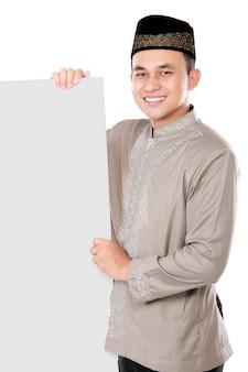 空白のボードを持って笑顔のアジアのイスラム教徒の男性