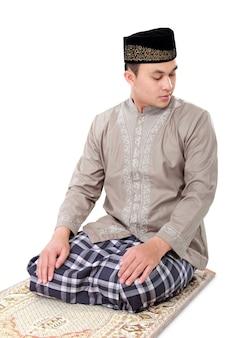 カーペットの上で祈るイスラム教徒の男性