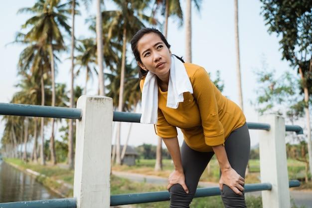 Женщина по беременности и родам делает перерыв после тренировки на открытом воздухе