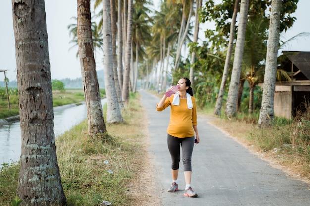 Беременная женщина пьет бутылку с водой во время тренировки
