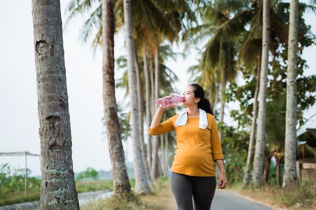 Беременная женщина после тренировки выпивает бутылку воды