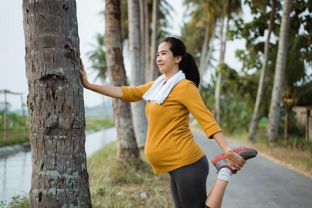 Беременная женщина растягивает ногу во время тренировки на открытом воздухе