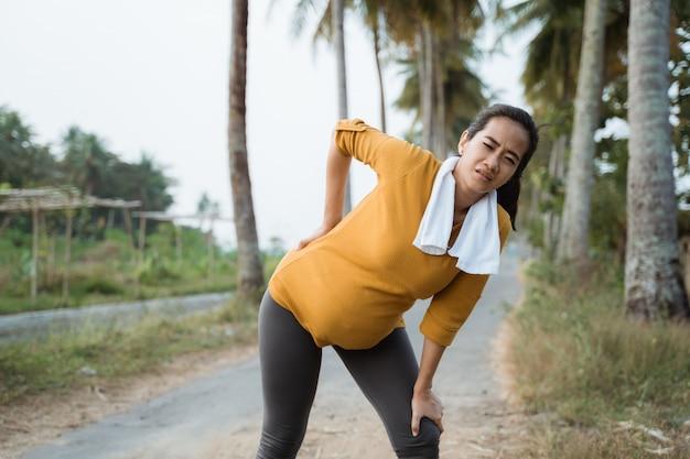 Боль в спине беременной женщины во время тренировки на открытом воздухе