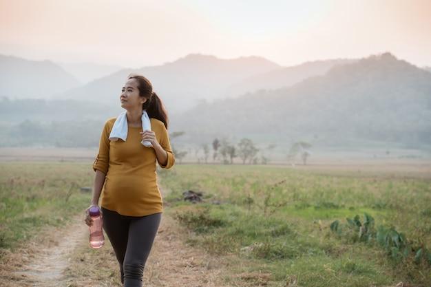 Беременная женщина, бег на открытом воздухе в природе