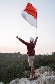 Азиатский мужчина с индонезийским флагом празднует день независимости