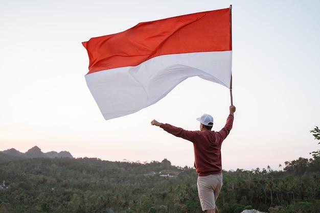 Человек с индонезийским флагом индонезии на вершине горы