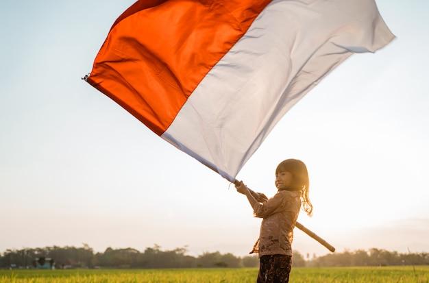 Маленькая девочка гордость хлопая индонезийским флагом от счастья