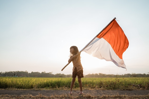 Азиатская маленькая девочка хлопает индонезийским флагом