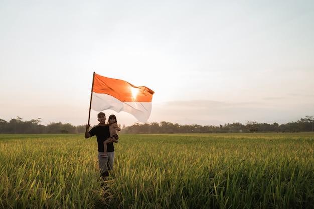 Отец несет маленькую девочку гордость хлопая индонезийским флагом счастья