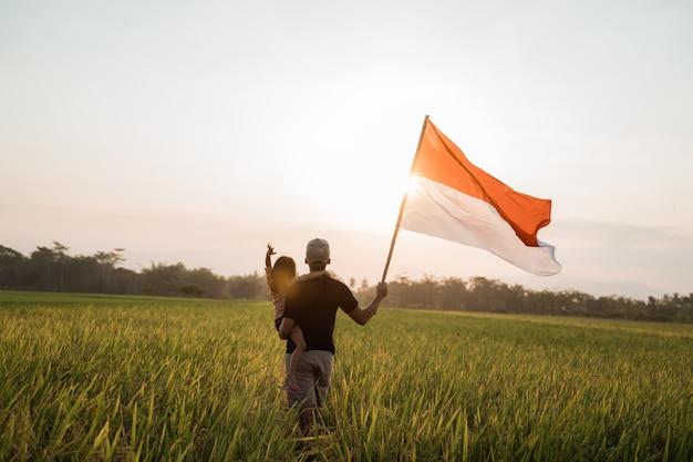 Азиатский молодой отец с дочерью хлопая индонезийским флагом