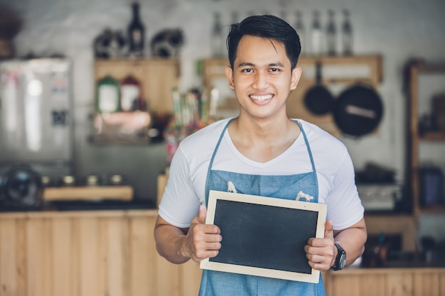 Азиатский мужчина владелец кафе с пустой доски